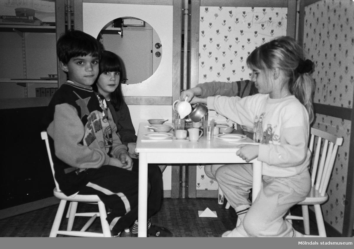 """Fyra barn sitter och """"fikar"""" vid ett barnbord. De har små kaffekoppar och fat på bordet och ett barn häller upp kaffe från en liten kittel av metall. I bakgrunden ser man en utvecklad avskärmningsdel som är klädd i olikfärgade tyger. Katrinebergs daghem, 1992."""