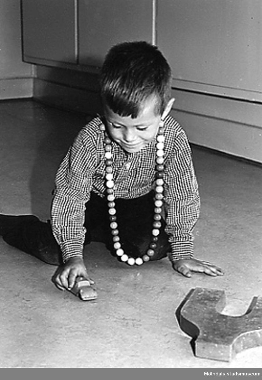 En pojke som leker med bilar på golvet vid Holtermanska daghemmet 1953.