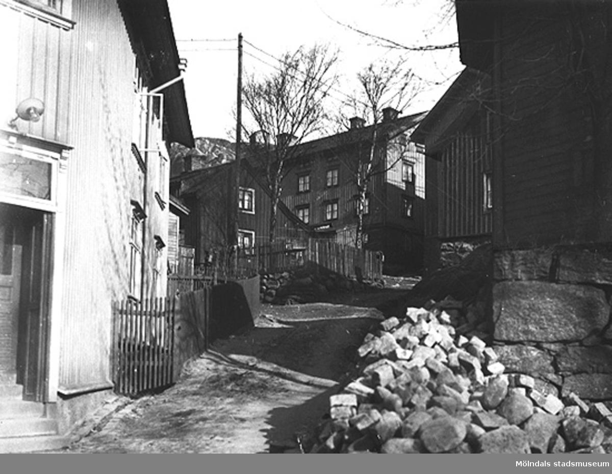 """Man ser """"Spanåsliden"""" även """"Smed-Kalles lid"""" eller """"Järnhandelsliden"""" som gick uppfrån Kvarnbygatan och in i Roten F. Till vänster Kvarnbygatan 27 (Johanssons järnhandel) och till höger Kvarnbygatan 29 (gamla rådhuset), 1900-1930-tal."""