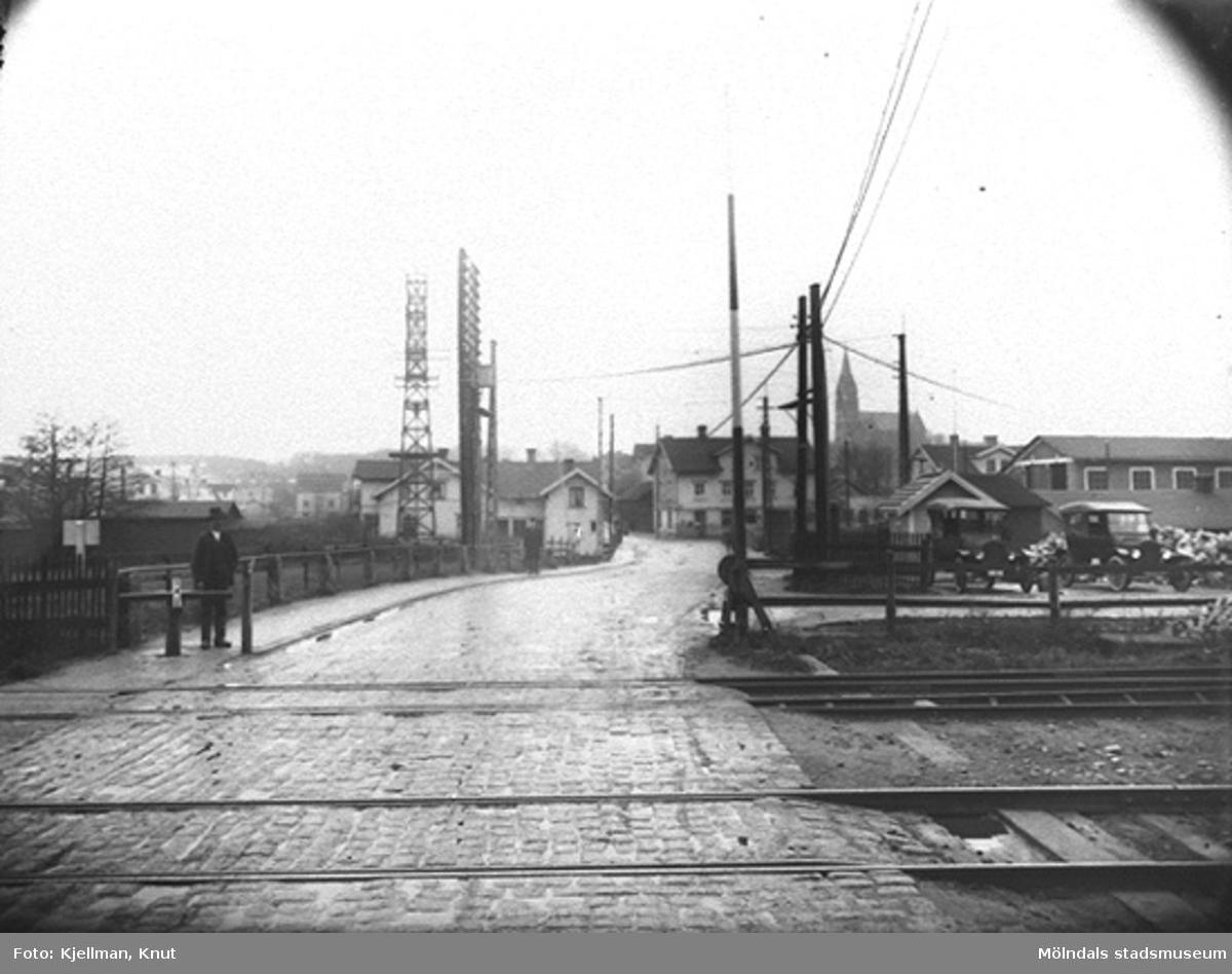 Järnvägsövergången vid Mölndals nedre, 1920-tal. Fotografen har stått på Kvarnbygatan strax öster om järnvägsspåren och fotat mot väster. I bakgrunden ses Kungsbackavägen 1 samt Göteborgsvägen 1 och 3 och framför spårvagnshallarna.
