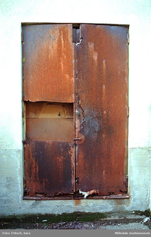 En rostig och trasig dörr i Mölndals Kvarnby, 1996.