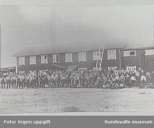 En grupp arbetare framför en byggnad på Myrnäs ångsåg.
