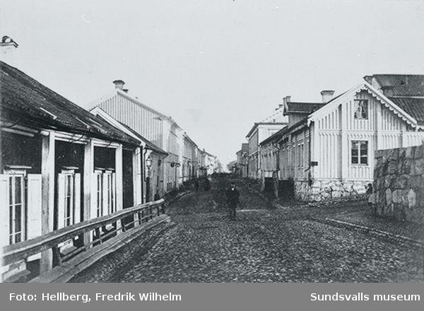Storgatan mot öster. I huset till höger bodde bagaren och fotografen Fredrik Wilhelm Hellberg. Fotoateljén med ett stort fönster mot norr fanns i ett gårdshus bakom bageriet. Byggnaden brann ned 1878. Efter detta byggde Hellberg ett stenhus på samma tomt som även överlevde branden 1888.