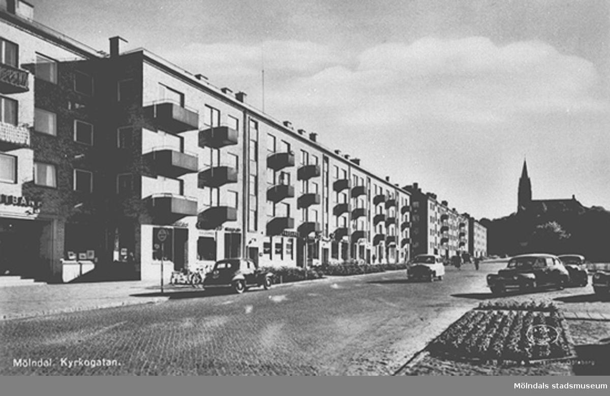 Vy över Kyrkogatan (nuvarande Tempelgatan) från nordost. Husen uppfördes i slutet av 1940-talet och gatan bytte namn 1954. Mölndal. Kyrkogatan. ÄKTA FOTOGRAFI   A-B Jolin & Wilkenson. Göteborg.