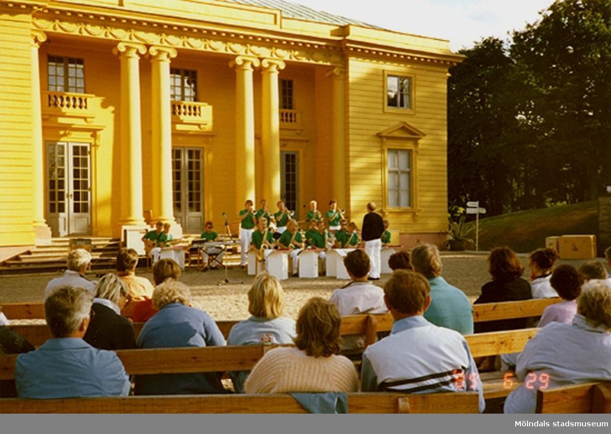 Publik sitter och lyssnar på musikunderhållning som pågår på scenen framför slottet.