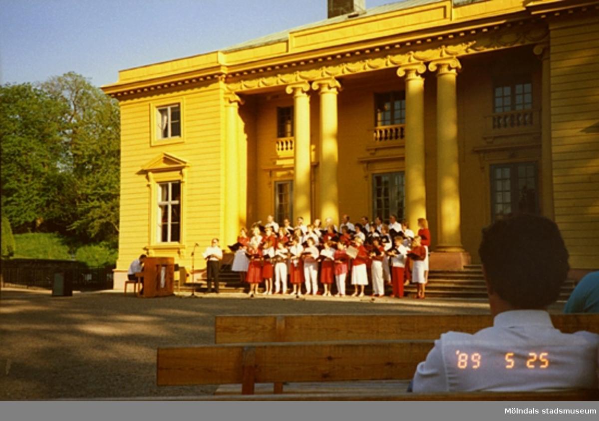 En röd- och vitklädd kör står framför slottet och sjunger inför publik.