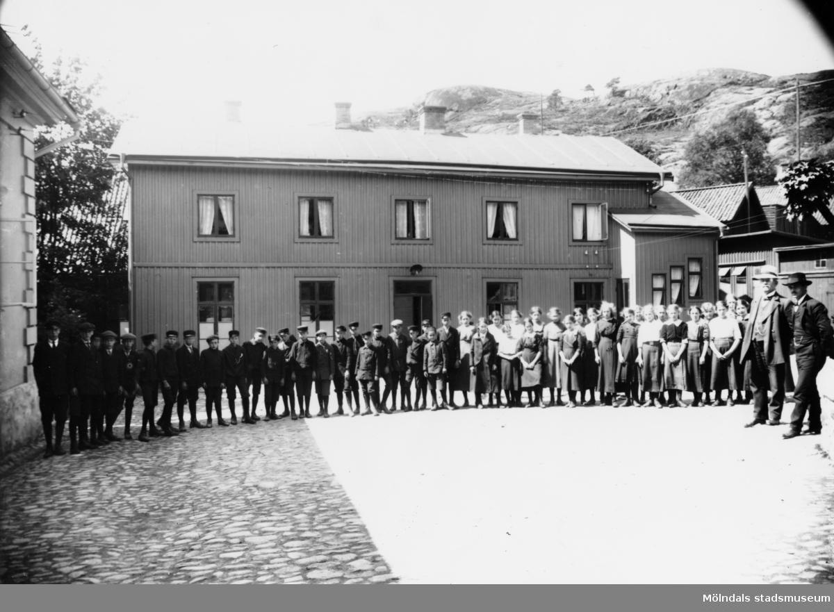 Götiska förbundets skola. Skolbarnen står uppställda framför skolbyggnaden. Till höger ses rektor Hallengren.