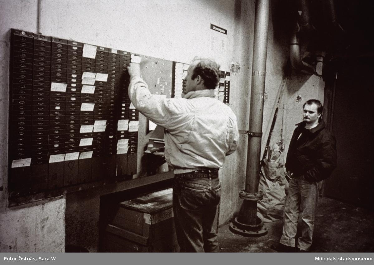 Jan Callesen och Peter Forsberg vid tavla med stämpelkort på Papyrus i Mölndal, år 1990.
