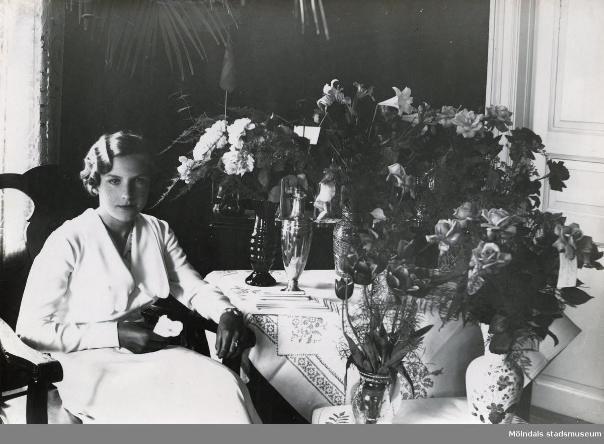 """Foto ur album som tillhört Edit Melin med bildtext:""""Jag som konfirmand med alla mina vackra blommor.""""Edit Viola Persson föddes 31/10 1918. Hon växte upp på Wallinsgatan i Mölndal där hennes far Verner Persson ägde och drev en handelsträdgård. Modern Hette Elvira men kallades Vera. Edit hade två bröder, storebror Fritz och lillebror Per Olof """"Pelle"""". Hon arbetade åt sin far redan som barn med grönsaksodling o. dyl. """"Vi fick trycka ner folkskiten runt gurkorna med bara händerna"""", berättade hon. Verner var mycket sträng och barnen fick jobba hårt. I ungdomen gick hon på Wendelsbergs folkhögskola. Hon träffade Åke Melin från Kållered som tillsammans med brodern Gösta Melin hade Bröderna Melins Vattenfabrik. Åke och Gösta drev även ett mindre cementgjuteri och sågade is på Tulebosjön om vintrarna. Edit och Åke gifte sig 28/6 1947 på Slottsvikens pensionat. Paret fick två söner, Lars Åke och Sven Olof (Olle). Under några år på 1950-talet ägde hon Edits Blomsterhandel på Sanatoriegatan 27 i Kålltorp. Hon jobbade sedan i vattenfabriken tills den lades ned 1974. Edit avled 11/10 2000 efter en tids sjukdom."""