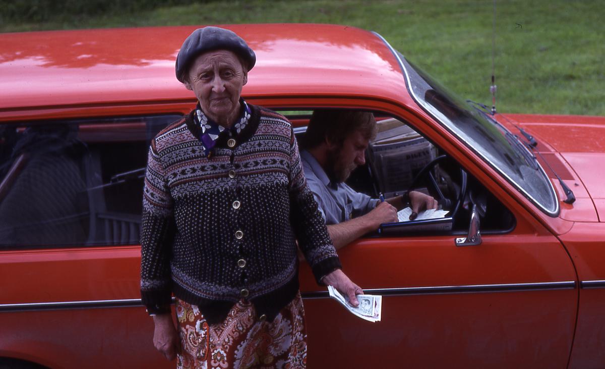Lantbrevbärare Mikael Mattsson har kommit till Vågsjö. Han sitter i bilen med nedvevad framruta och Elsa Wanzelius står utanför.