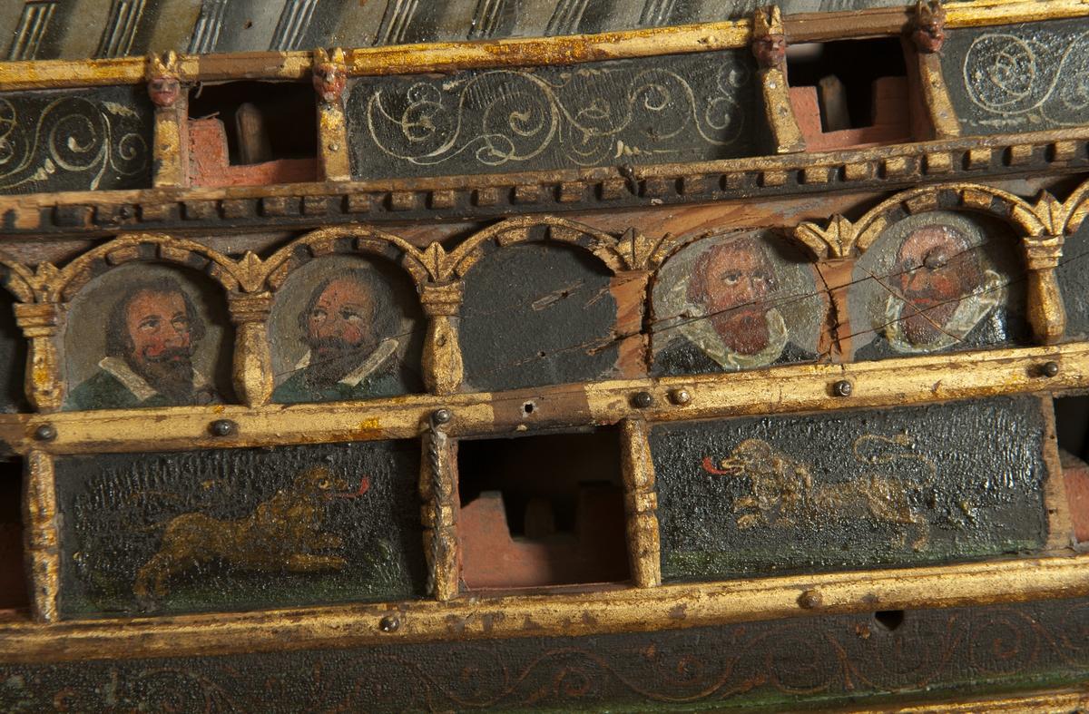 Fartygsmodell, votivskepp. Hel, i urholkat block av trä, endast skrov, utan master och rigg. Av fockmasten och mesanmasten kvarstå stumpar, avbrutna vid däcket. Rodret och galjonen saknas. Huvuddäck med stor öppen lucka, halvdäck med trallverk, kvarterdäck med poop. Högt förkastell med trallverk i däcket. Alla däck svarta. Sida mörk. Botten i gulnad vit färg, med vågad vattenlinje.