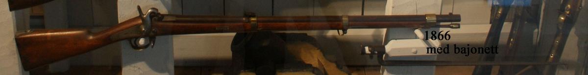 """Gevär, 1855 års modell, s.k. miniégevär, märkt: """"2066"""". Kolven av trä, pipa och mekanism av stål. Beslagen av metall. Slaglås. Pipan räfflad med fyra räfflor, längd 880 mm. Stickbajonett, längd 610 mm. Kaliber: 16 mm. Vikt: 4,4 kg. Hela längden: 1225 mm."""