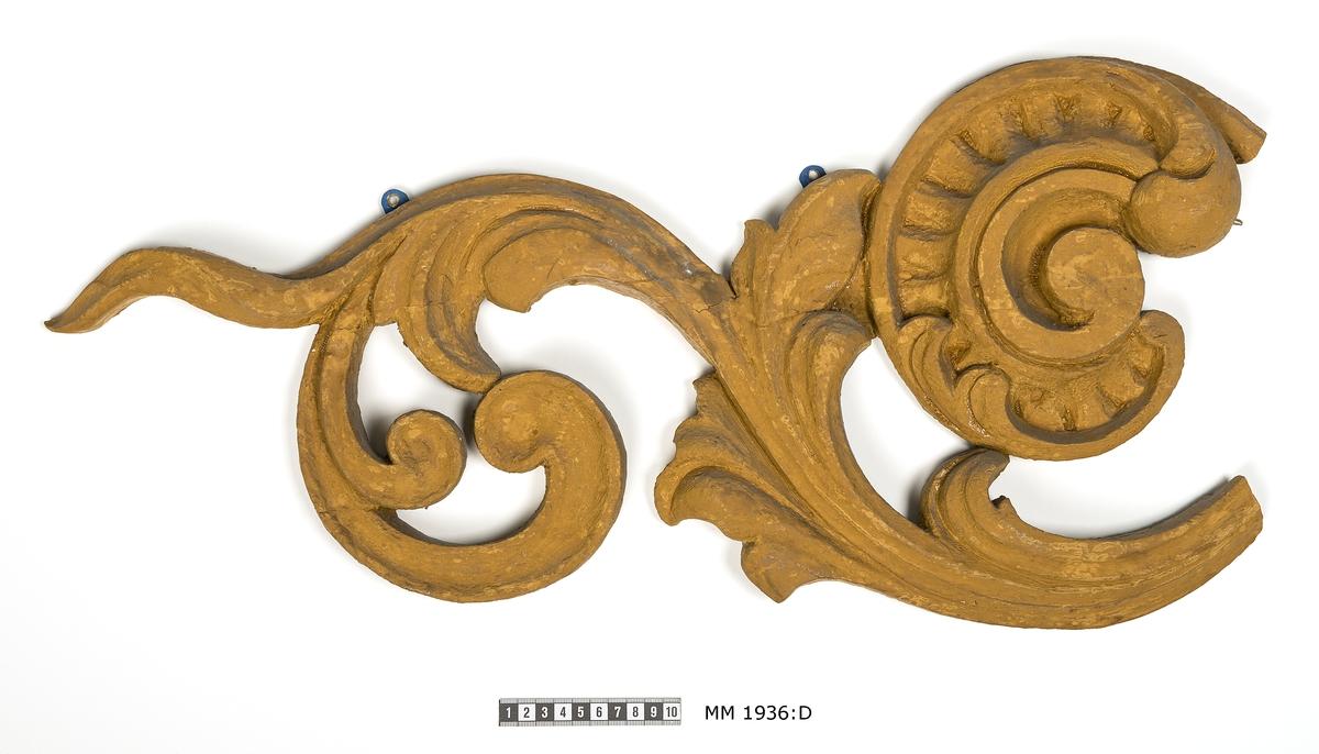 Akterstävsornament i fyra delar av furu med gul grundfärg. Det är utskuret i blommor, rankor, blad och snäckor. Har förmodligen tillhört någon korvett från 1800-talet och suttit på båda sidor av akterstäven med sköld eller monogram i mitten. Det renoverades 1952, varvid det hoplimmades och gamla färglager togs bort.