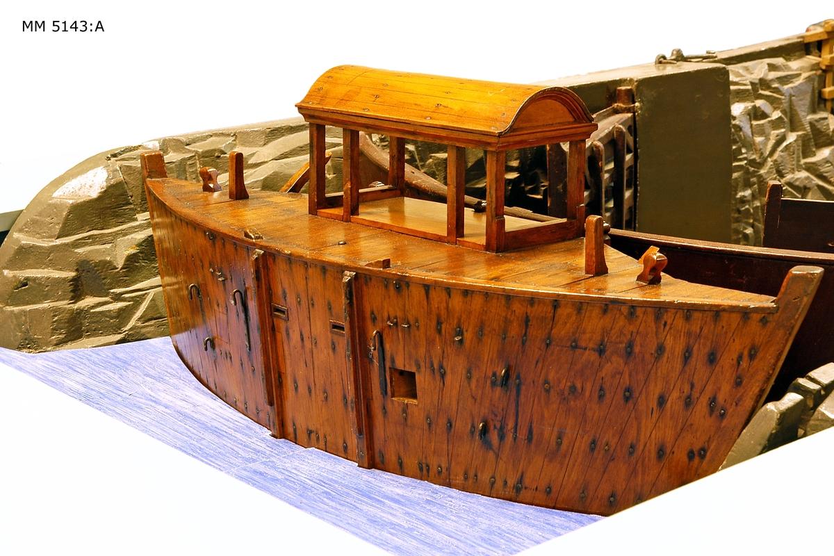 Modell av den s.k. Gamla dockan, eller Polhemsdockan på Lindholmen å Karlskrona örlogsvarv. Modellen försedd med sätt och lyftanordning för denna. Dockan byggd åren 1716-1724 efter planer av Christoffer Polhem och Charles Sheldon. Ang. dockans tillkomst se bifogade upplysningar. Modellen tillverkad i två delar. Den är målad i mörkgrått, portarna fernissade. Blockraden i botten och trappan ned av omålat trä.