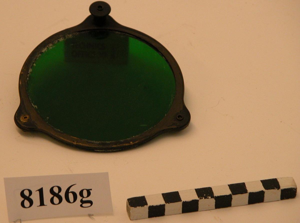 Metallram som innefattar ett grönt färgat glas. Metallramen har tre öron. På två av dem sitter hakar som fäster runt lampans fläns. På det tredje sitter en fjäderbelastad kolv som kan dras ut och sedan fäster utanför flänsens kant.