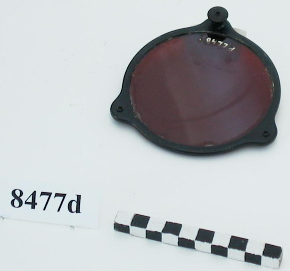 Metallram som innefattar ett rödfärgat glas. Metallramen har tre öron. På två av dem sitter hakar som fäster runt lampans fläns. På det tredje sitter en fjäderbelastad kolv som kan dras ut och sedan fäster utanför flänsens kant.