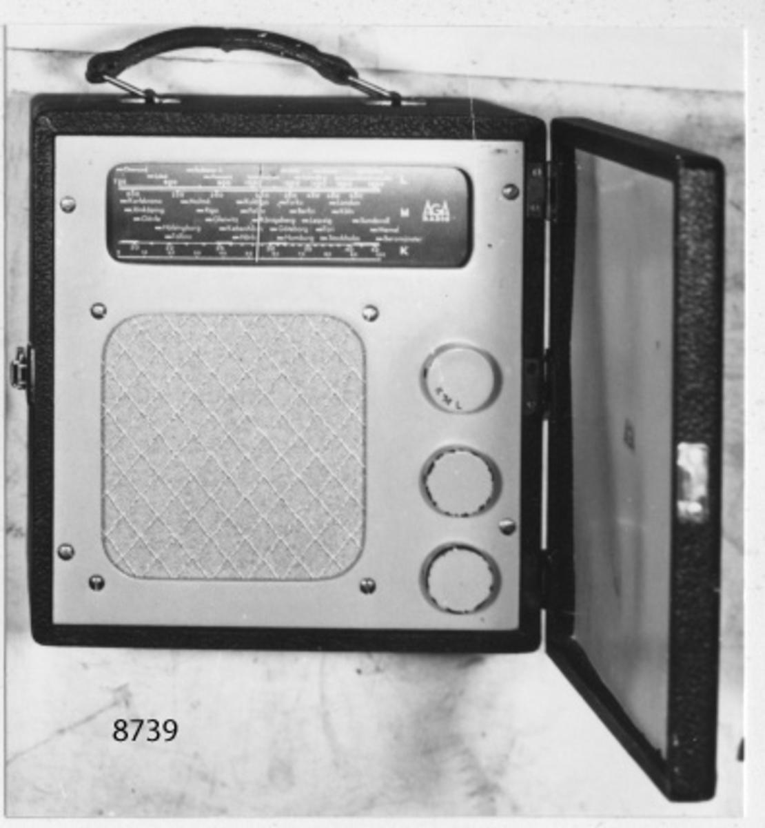 Batteridriven. I låda av trä, klädd med svart papper, dörr på framsidan, bärhandtag av läder. På panelen rektangulär skala för lång-, mellan- och kortvåg samt tre rattar. På innersidan av bakstycket beskrivning för glödströms- och anodbatteriernas inkoppling. Skalan märkt: Aga radio. I botten märkt: Typ 240.