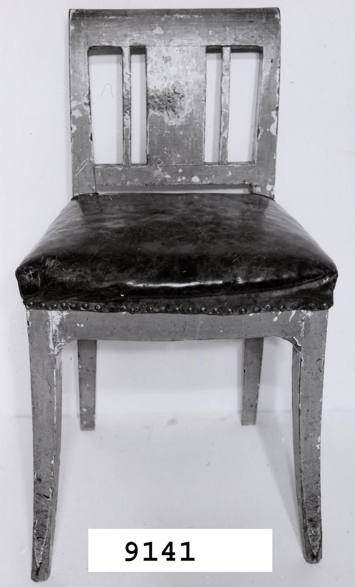 Stol av trä, gulmålad och fernissad. Sitsen klädd i mörkbrunt skinn. Fyrsidiga framben svängda framåt. Fyrsidiga bakben och ryggstöd svagt svängda bakåt. Ryggstöd av fem delar, sammanhållna av två tvärslåar. Från 1800-talet.
