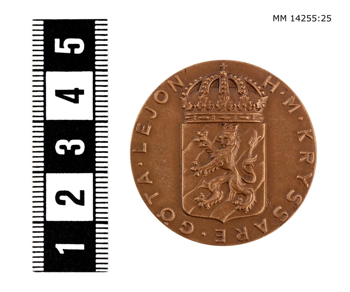 Medalj i brons. På framsidan vapenskjöld med lejon, krönt av kunglig krona jämte omskriften H. M. KRYSSARE GÖTA LEJON. På baksidan koncentriska ringar, däremellan inskriptionen ME NEMO IMPUNE LACESSET (Ingen angriper mig ostraffat). Foto: Se mm 14255:1.