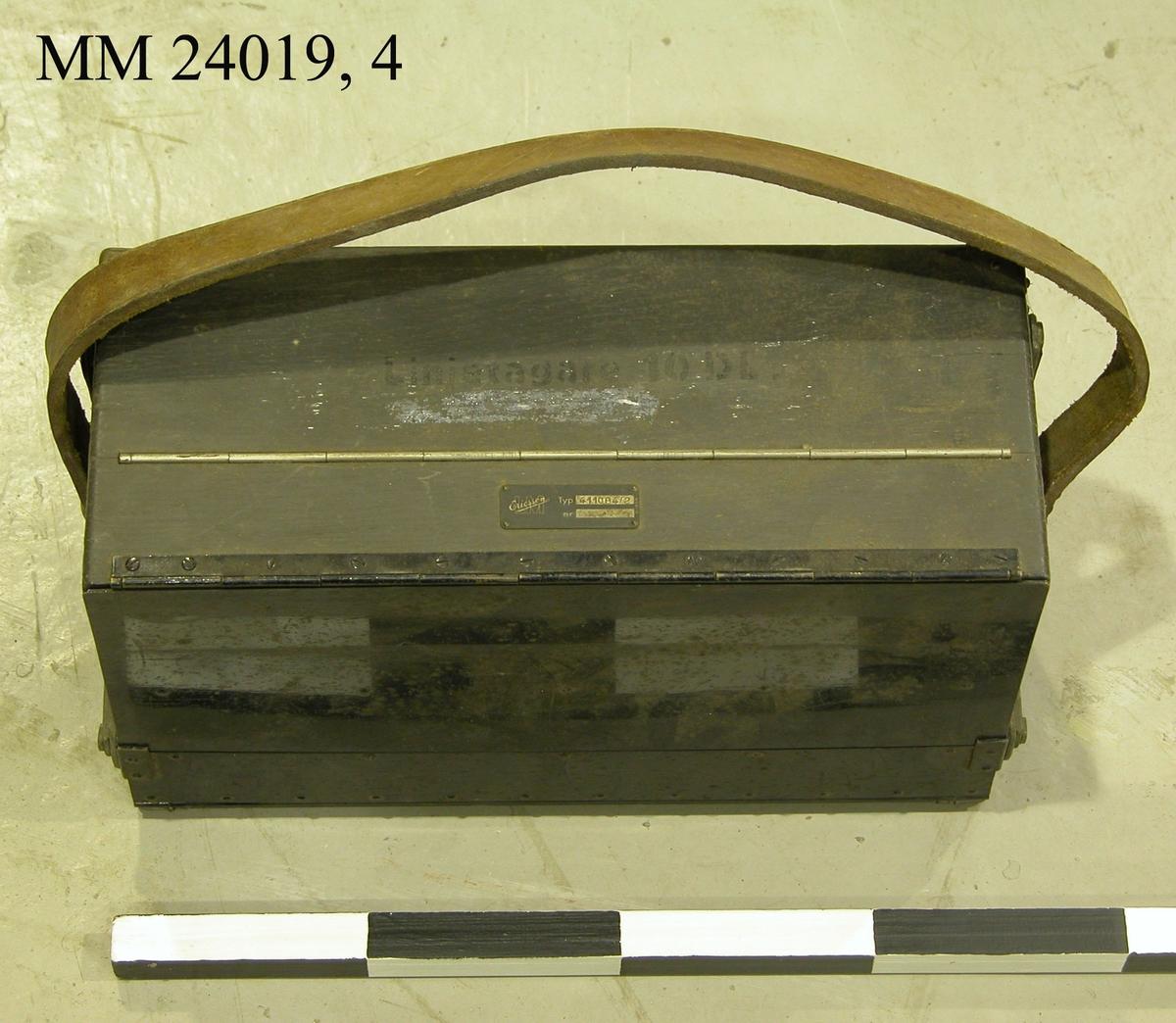"""Svart metallåda på framsidan märkt med målad vit text: """"LINJETAGARE 10DL"""". Under texten finns även en mindre metallplatta med texten: """"LM Ericsson, Typ 411084/2"""". Manöverpanelen är försedd med tio stycken numrerade Från/Till reglage. En orange gummislang försedd med en elkontakt i ena änden är ansluten till manöverpanelen. En liten svart vev av metall ligger lös inne i lådan. Lådan går att öppna stegvis via olika metallspännen. Lådan är försedd med en bärrem av läder. Se även MM 24019, 1-3."""
