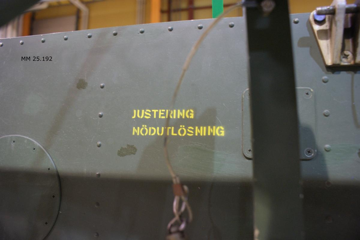 """Grön metall balk. Rektangulär och tämligen platt. På undersidan fästanordnignar för en torped som utgörs av armar och skruvar. På sidan som ska vara mot helikoptern märkning på blå dymoremsa: """"12. HKP-DIV"""". Dessutom schablonmärkning i gult såsom """"Särkingspinne"""" med mera. På sidan som ska vara från helikoptern märkning """"Justering och kontroll nödutlösning"""" med mera. Metallbricka på övre delens ena kortsidan anger materielnummer F1462-001101. Övre delen benämns Balk V, individnummer 004. Nedre delen benämns kombilavett, materielnummer F1341-228791. Individnummer på kombilavetten 25."""