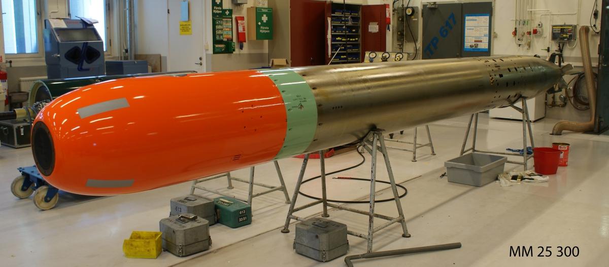"""Torped 613, övningsversion. 53 cm torped med övningsdel i fören, orangemålad. Övningsdelen märkt: """"613-4031"""". Metalldelen stämplad: """"61 3352"""". Grönmålad elektronikdel  intill övningsdelen märkt: """"Zonrör 80,1 613-3352"""". Akterdel med dubbla propellrar."""