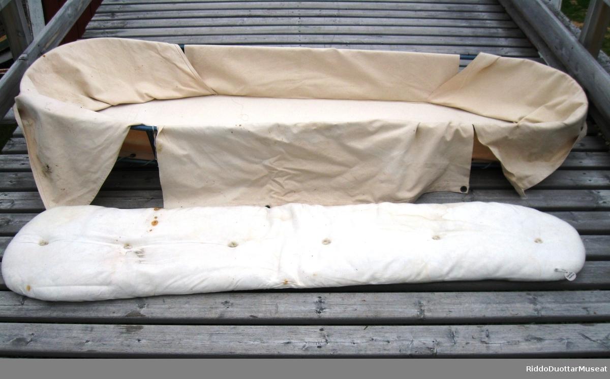 """Sykebåra har ramme av jernrør. Naturhvit seilduk av bomull er """"sydd"""" sammen med ramma med nylontau. Messingmaljer forsterker hullene. En madrass blir holdt på plass av seilduken. Madrassen er laget av naturhvit bomull med vattstopping.  Ramma er merket med hvite versaler på rød bunn ved hodeenden på høyre side: """"KOKELV SANITETSFORENING, KOKELV""""."""