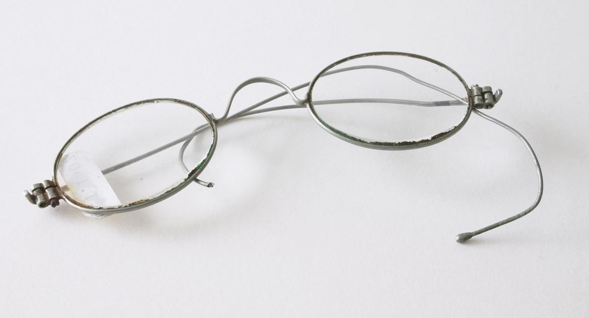 Et par gamle briller. Brukes til å lese eller se bedre. Små ovale glass - innfattet i sølv/stål ramme og stang.Den venstre stangen noe defekt.