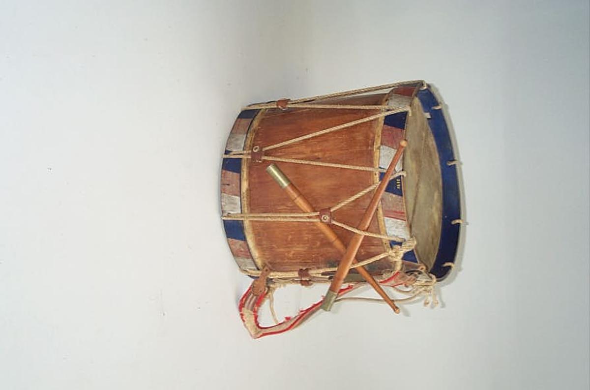 Stor hjemmelaget tromme  Stor tromme, sammensatt av sammen- limede lindetræs staver. Høide 42,5 cm, diameter 41,7 cm. Paa messinglaaset indgraveret E.S.G. Trægjorden i begge ender i senere tid malet i nationale farver. Har i lang tid været benyttet som militær-tromme av tambur fra Leikanger. Kjøp av Elling S. Gjerde, Hermansverk. Trommestikkerne, der er dreiet, har sølvholker i enderne.
