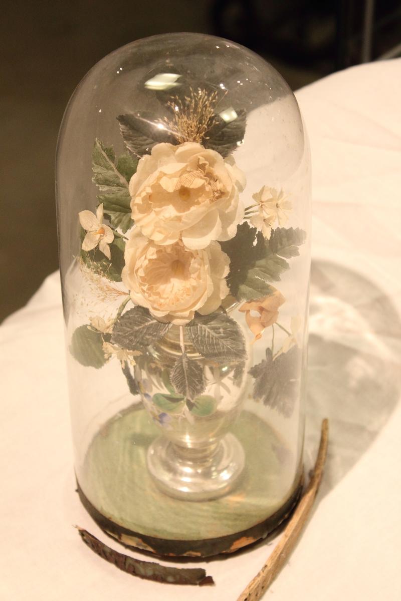 """En """"Glassmonter"""" med en blomsteroppsats i vase inne i. Blomstene ser ut som silkeblomster. Den har vært lukket av en ring i tre."""