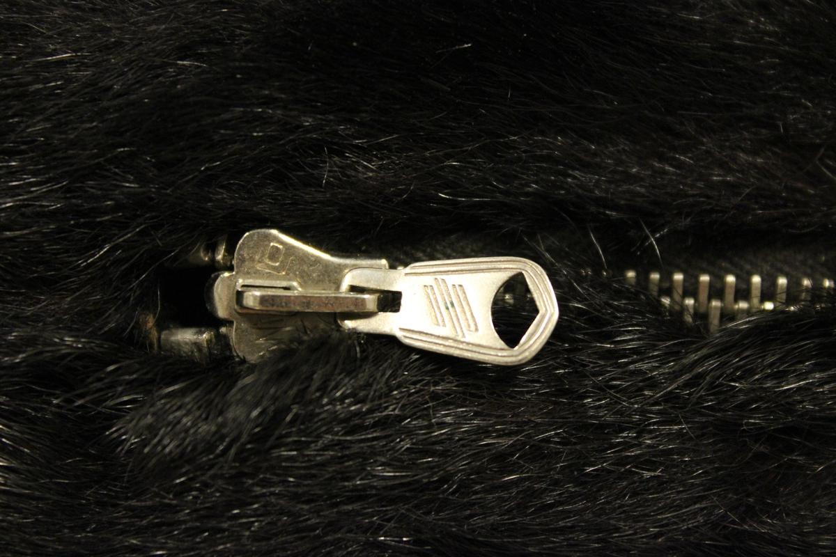 """Muffe i sort minkpels med glidelås på ene siden for oppbevaring av feks. mynter. Har tilhørt """"Gulovna Edwarda Giskedal"""" f.15.09.1885 - d.1977. Var gift med """"Oluf M. Mydland"""""""