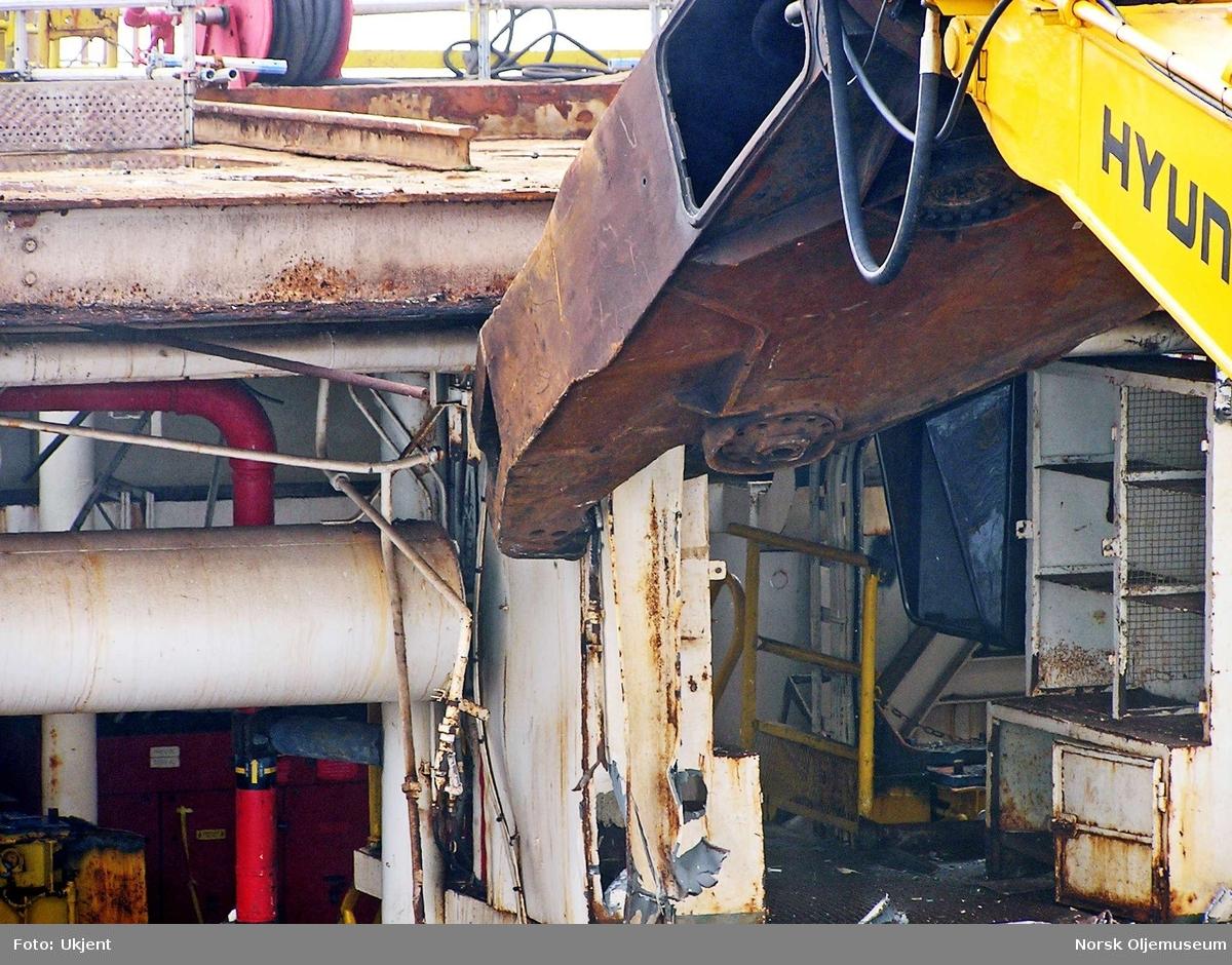 Rivingen av DP2 har startet. En hydraulisk saks er montert på en gravemaskin, og er her i ferd med å klippe deler av plattformen i små biter. Disse mindre bitene plasseres i containere for transport til fastlandet. Foto fra juni måned 2005.