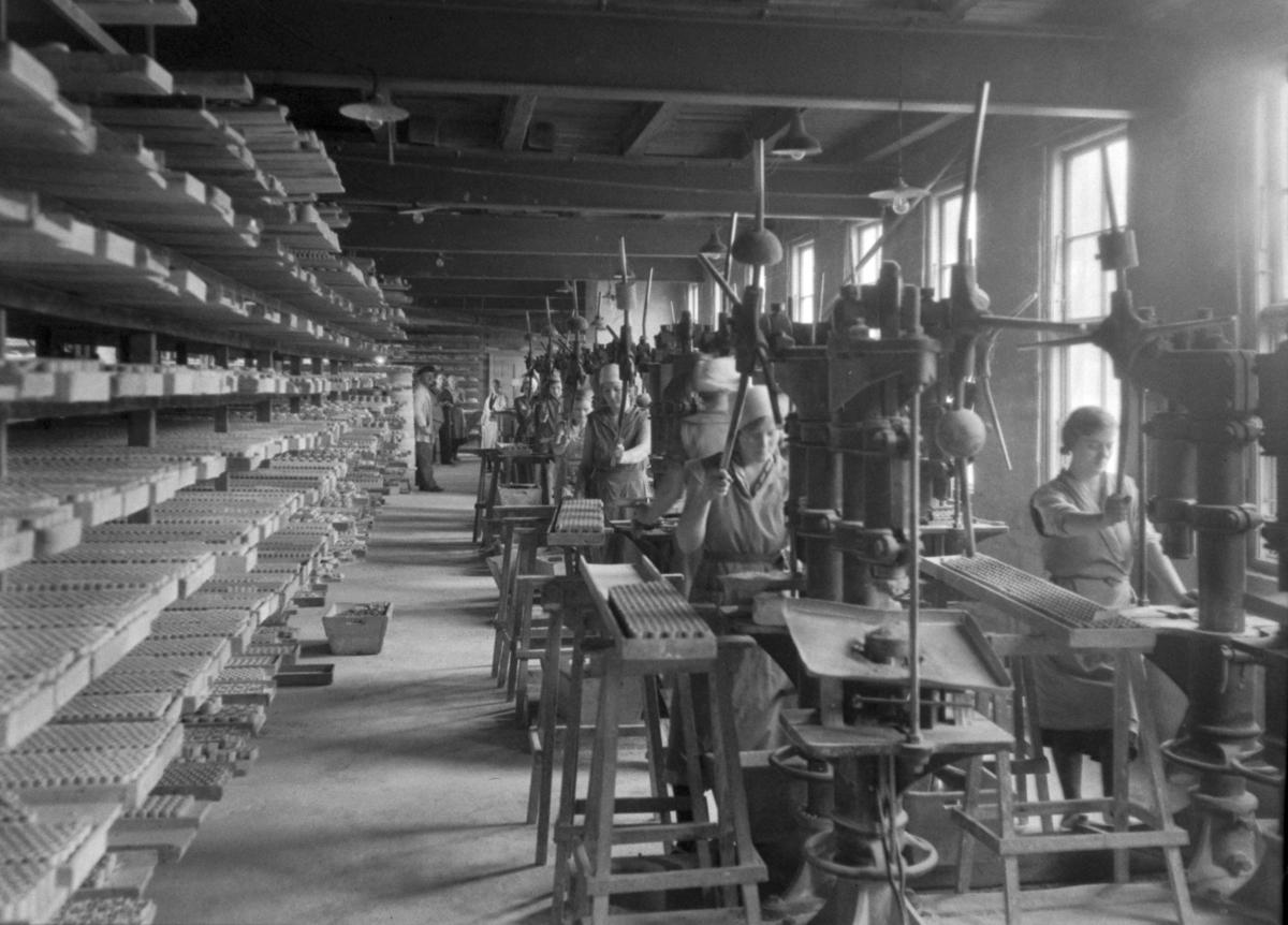 Kvinner i arbeid ved maskiner ved Norsk Teknisk Porslensfabrikk.