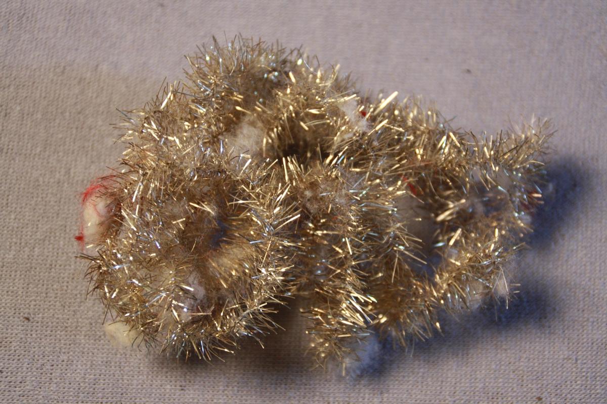 Glitterremser med rester av bomull og rødt stoff på.