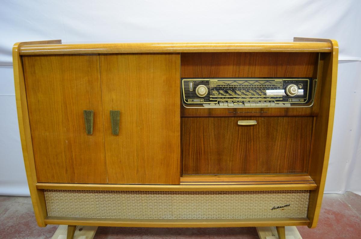 Radio innfeldt i sjenk. Lakkert. Skyvedører. Halve sjenken består av radionen, medan andre halvdelen har hyller. I hyllene stod det ein båndopptakar (KSF.011205).