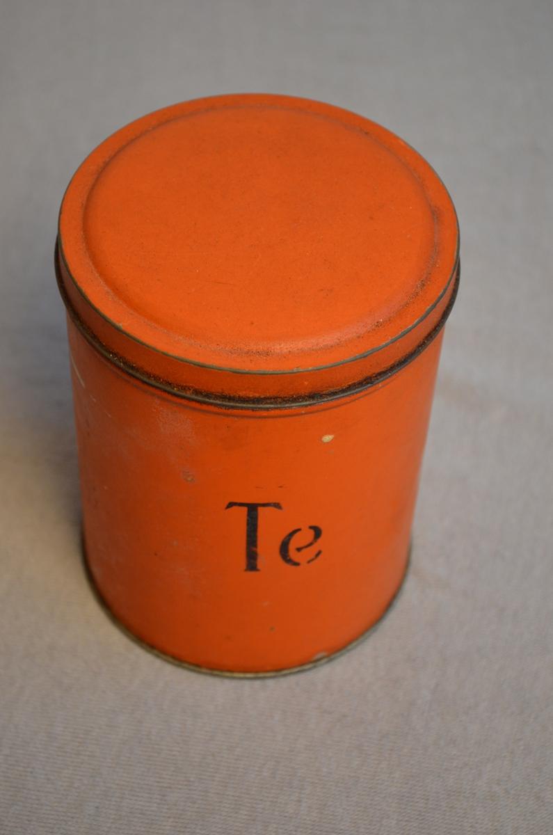 Rund boks for oppbevaring av matvarer. Oransje farge. Det står Te på boksen. Målinga er skrapt av enkelte plassar. I boksen låg det framleis te, noko laus te og ein pakke. Pakken har fått reg.nr. KSF.011246. Har blitt lagt opp igjen i boksen.