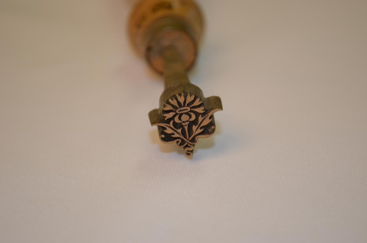 Stempel i jarn med treskaft. Motivet er ein blome. Mest truleg nytta til dekorering av skinnpermar til bøker. Denne låg i ei verktøykasse frå ein boktrykkar.
