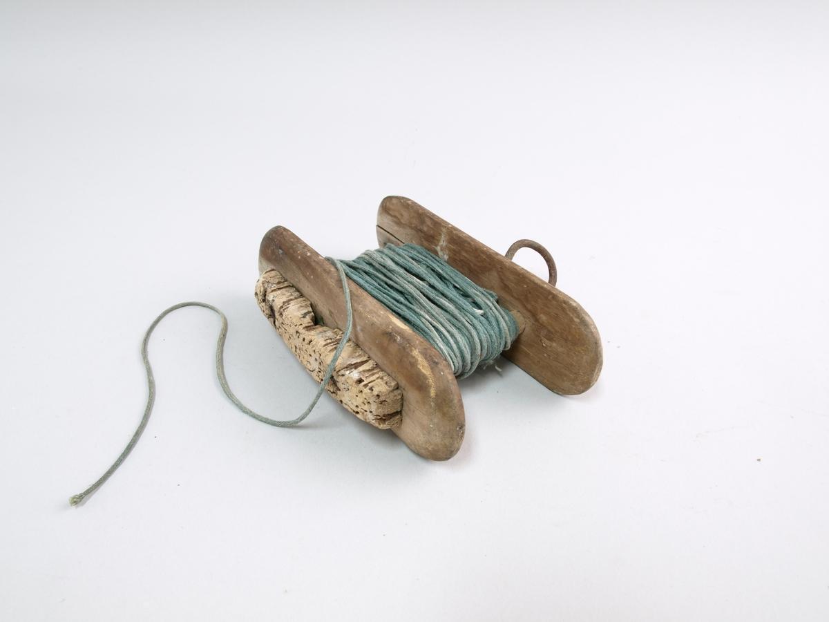 Fiskevinne i tre med kork. To delar i tre med trespiler og jarnbolt mellom.  Jarnkrok i eine enden. Det er tvunne ei snor over mellomverket. Snora er truleg laga med slingrestokkar. På eine treenden er det kork. Reiskapen er slik at snora kan dragast fort av, då snurrar midtre delen rundt.