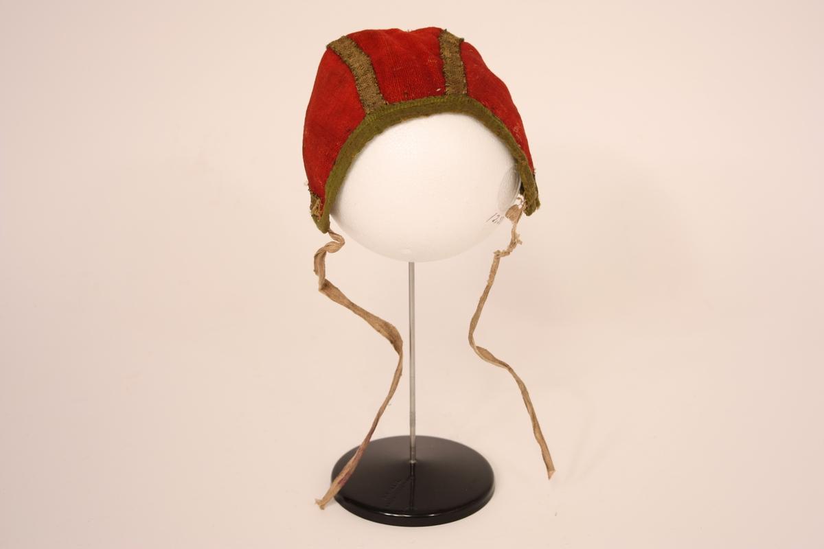 Kyseform. Raudt bomullsstoff med grøne kantband i silke. Dekorert med gullband og 2 små krossar i perlebroderi. Fora med rutete bomullslerret. Påsydde hakeband i bomull.