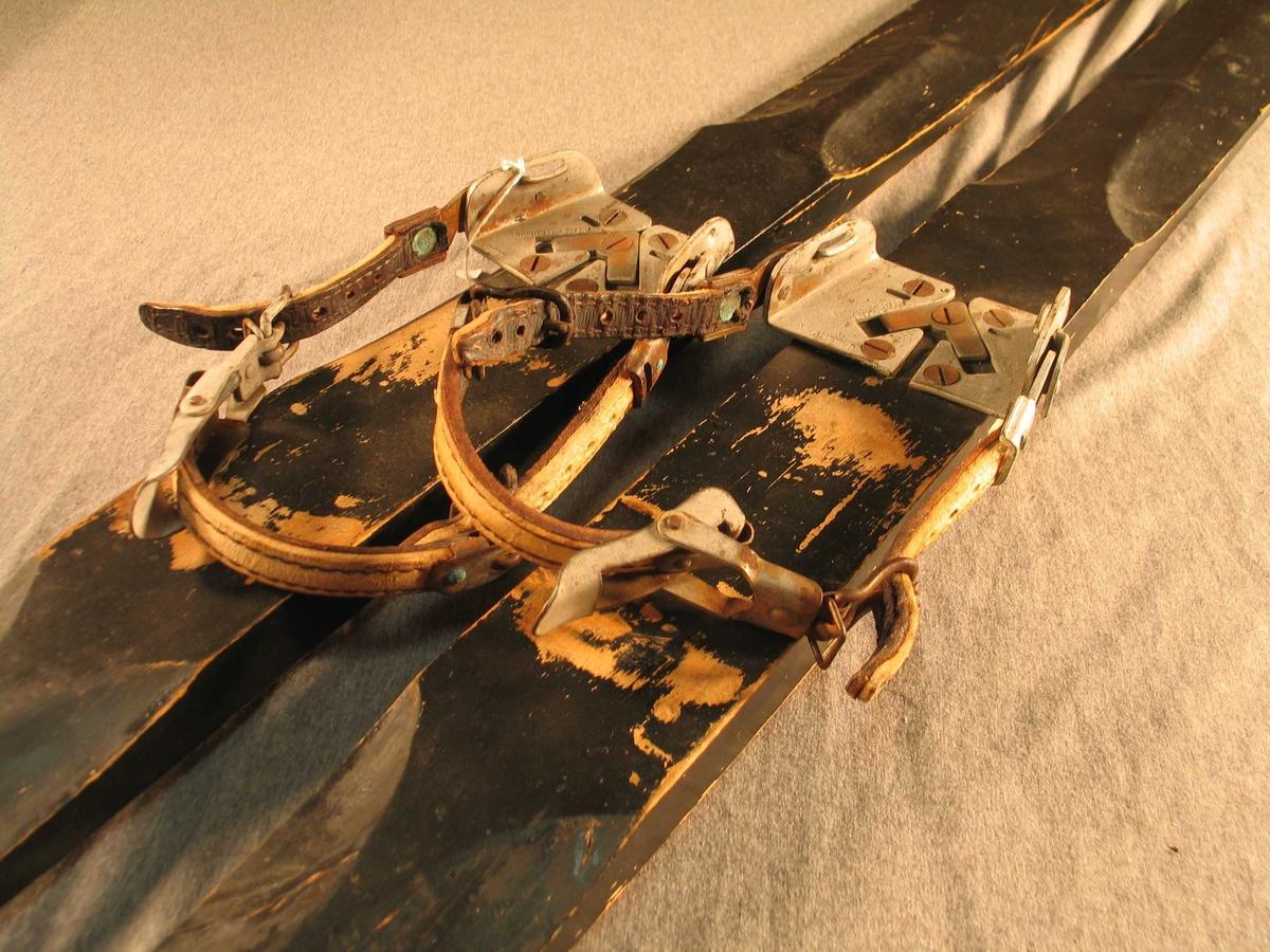 Svartmåla ski med Polar-bindingar med hælreim i lær. Tuppen på skiene er enkel med fortjukning, bakenden er plan og rett avskoren. Oversida av skiene har bogeforma rygg både framom og bakom bindingen. Under har skiene enkel sirkulær rand.