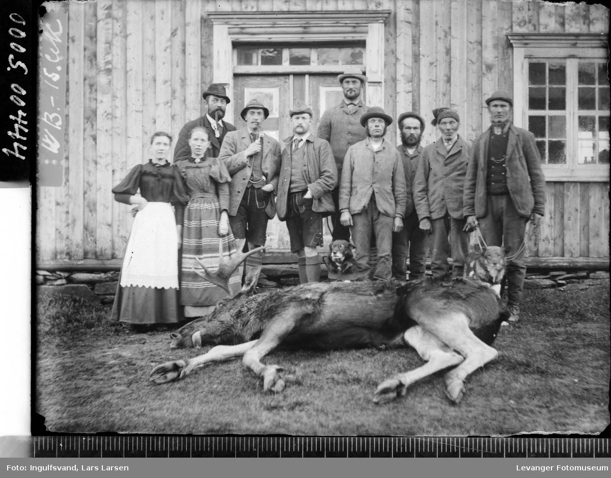 Gruppebilde av ti mennesker og to hunder foran en inngangsportal, med en død elg i forgrunnen.