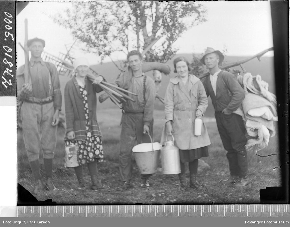 Gruppebilde av tre menn og to kvinner med jordbruksredskaper.