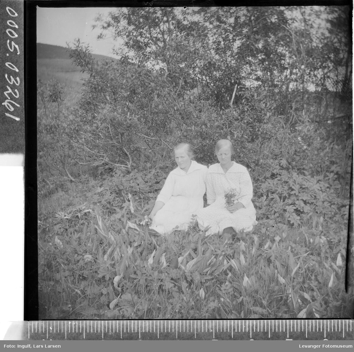 Portrett av to kvinner som sitter i gresset.