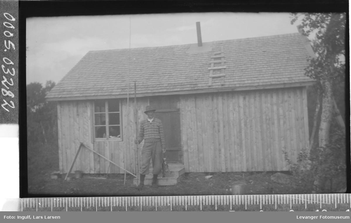 Portrettt av en mann med fiskestang og fisk foran en hytte.