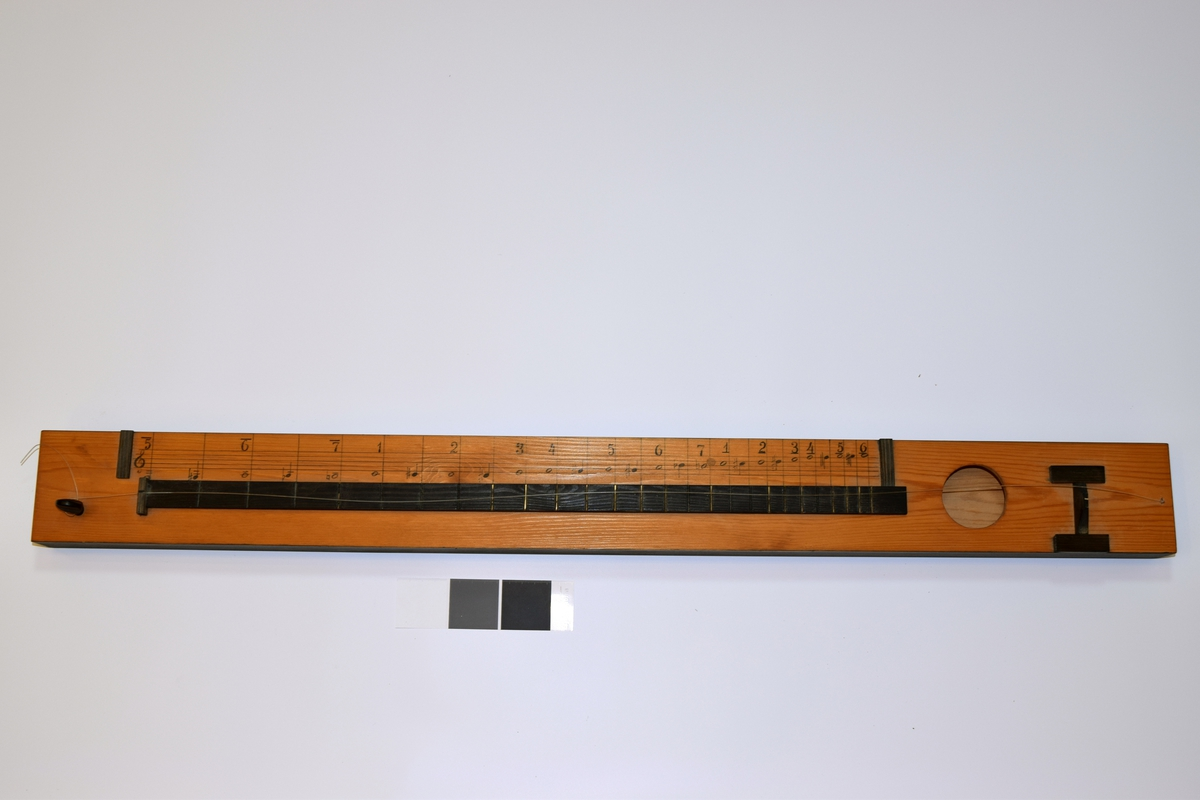 Rektangulær resonanskasse, med sirkelformet lydhull. En streng.
