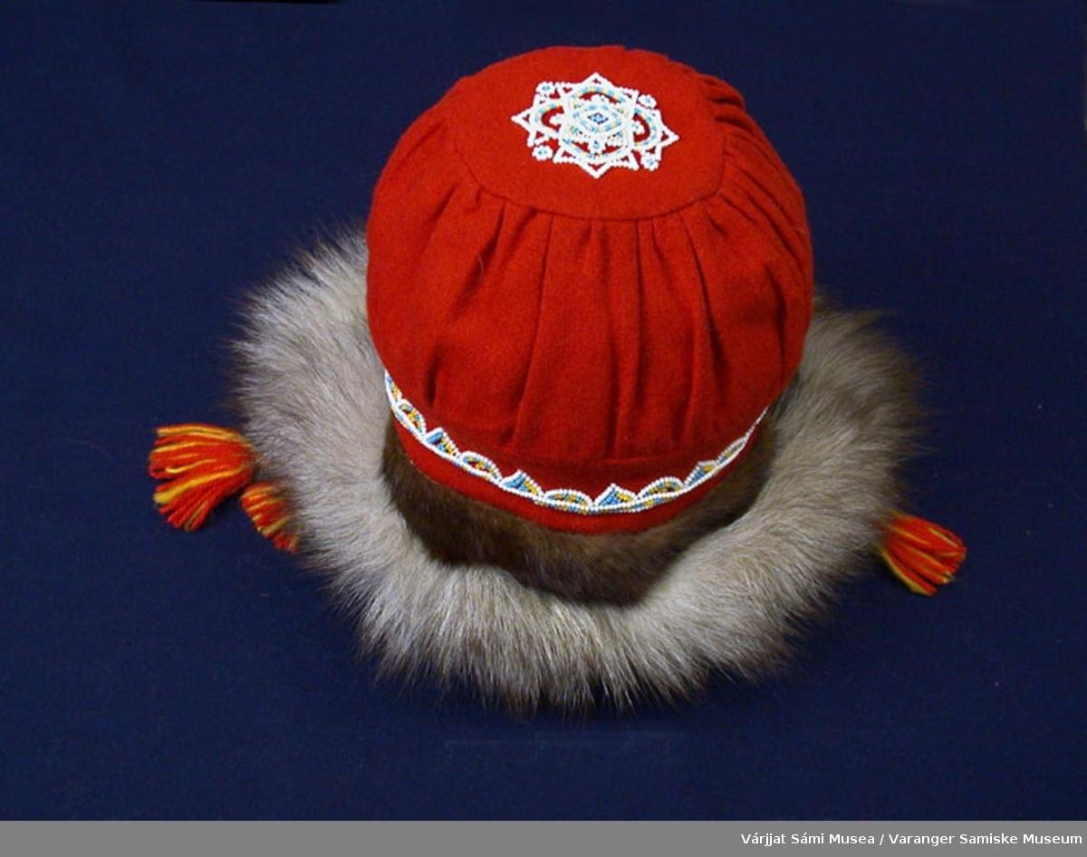Damelue av klede, revepels og minkpels. Lua sydd av rødt klede. Pyntet med perler oppå toppen av lua og rundt kanten. Pelskant rundt. Den har snorer av ullgarn i gult og rødt.