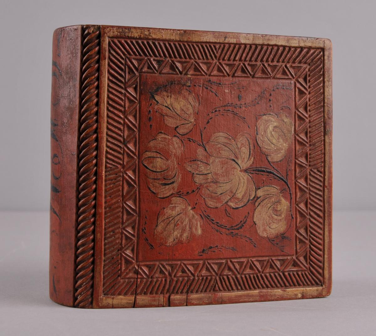 Skrin forma som ei bok. Skreielok i begge endar. Skrinet er raudmåla med karveskurd på begge sidene og rosemåling i kvitt og svart.