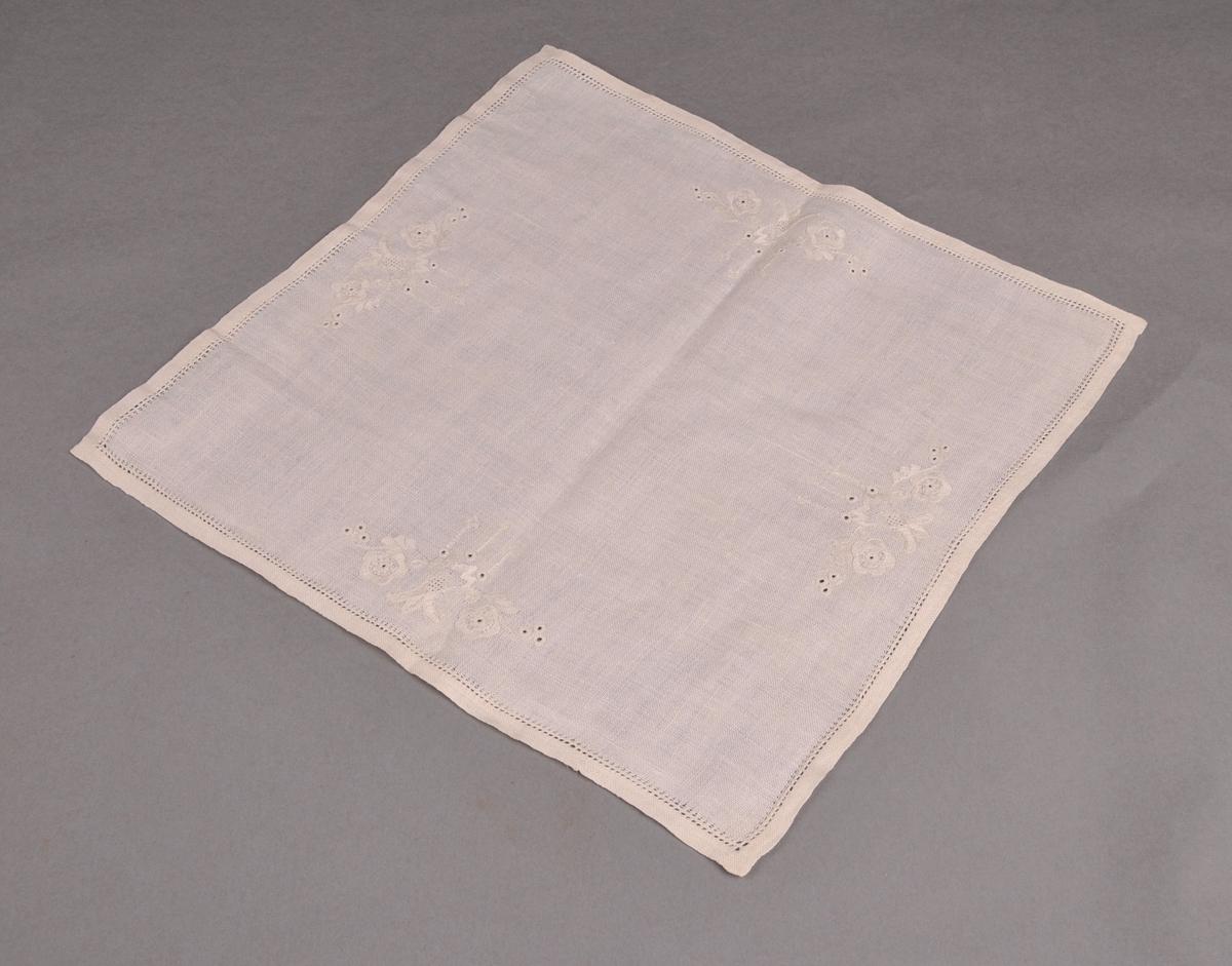 Brikke i lin med eit brodert motiv midt på kvar langside. Dobbelt bretta fald, sydd til med hand.