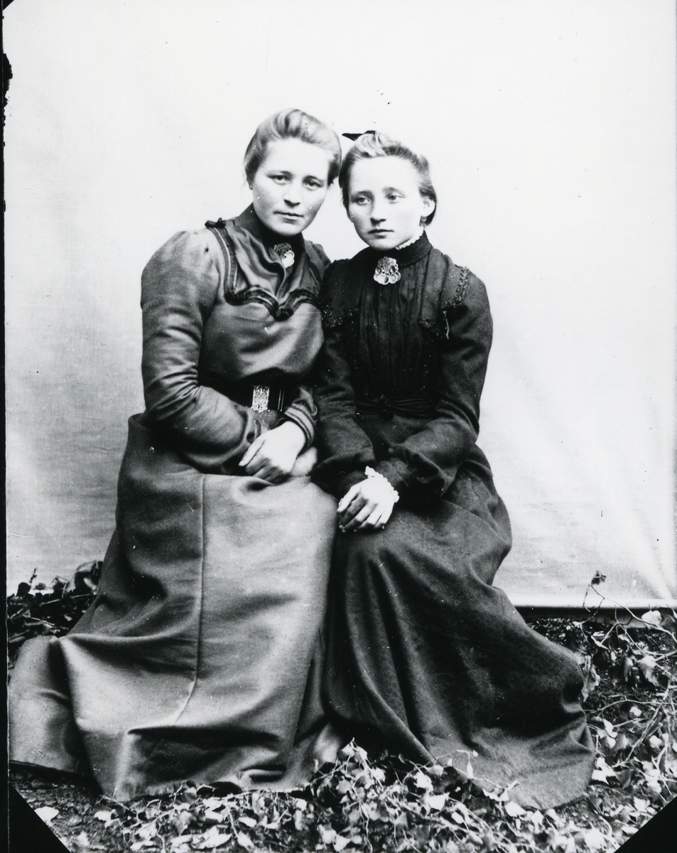 Kvinne og yngre jente sittende med hodene lent mot hverandre, lerretbakgrunn