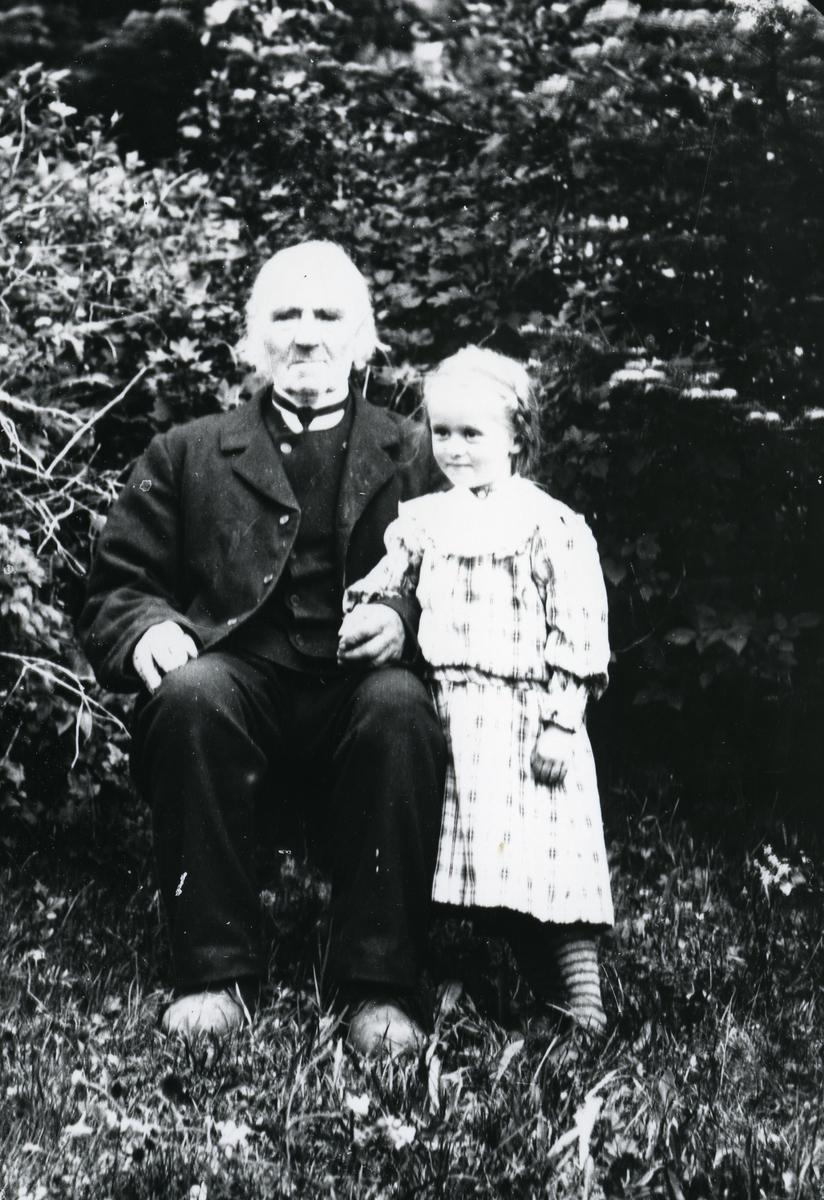 Mann med barnebarn, fotografert foran trær.